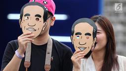 Dua pendukung calon Presiden no urut 01 Joko Widodo berpose mengenakan topeng berwajah Jokowi di Istora Senayan, Jakarta, Minggu (10/3). Acara Festival Satu Indonesia dibuka Presiden Jokowi. (Liputan6.com/Johan Tallo)