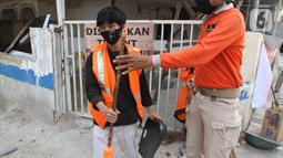 Petugas Satpol PP (kanan) menghukum warga pelanggar PSBB yang terjaring razia masker di Jalan Tanjung Duren Raya, Jakarta, Jumat (11/9/2020). Petugas Satpol PP gencar melakukan razia masker menyusul kasus COVID-19 di DKI Jakarta yang terus meningkat. (merdeka.com/Imam Buhori)