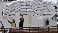 Buruh memindahkan beras impor dari kapal ke truk di Pelabuhan Barang Lembar, Lombok Barat, NTB, Rabu (26/1). Ribuan ton beras impor dari Vietnam akan digunakan untuk memenuhi kebutuhan raskin.(Antara)