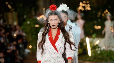 Bella Hadid berjalan di catwalk untuk show Rodarte pada New York Fashion Week: The Shows di New York City, Selasa (11/2/2020). Bella Hadid seolah-olah kembali ke era tahun 50an dalam balutan gaun polkadot merah dan putih dengan kerudung yang menutupi wajahnya. (FERNANDA CALFAT/GETTY IMAGES/AFP)