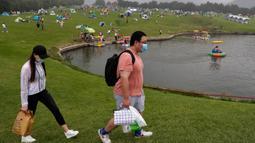 Sepasang suami istri melewati orang-orang yang berkemah di gunung yang indah di Yanqing, pinggiran Beijing, 30 Agustus 2020. China memiliki lebih dari 200 orang yang dirawat di RS karena COVID-19, dengan lebih dari 300 lainnya diisolasi usai dites positif terkena virus tanpa gejala. (AP/Andy Wong)