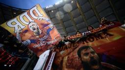 Suporter mengibarkan bendera bergambar gelandang AS Roma, Daniele De Rossi saat melawan Parma pada laga Serie A di Stadion Olympic, Roma, Minggu (26/5). Laga ini perpisahan bagi De Rossi dan AS Roma setelah 18 tahun. (AFP/Filippo Monteforte)
