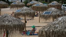 Panel surya terpasang pada sejumlah payung di pantai dekat Balai Kota Vari-Voula-Vouliagmeni, Yunani, Selasa (21/7/2020). Para pengunjung pantai dapat berkontribusi terhadap upaya penghematan energi menggunakan tenaga surya. (Xinhua/Lefteris Partsalis)