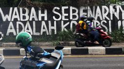 Pengendara melintas di depan mural yang berisi kritikan di Jalan Raya Bogor, Depok, Jawa Barat, Minggu (19/9/2021). Kritik terhadap pemerintah lewat coretan dinding atau mural sempat menjadi polemik karena dihapus. (Liputan6.com/Helmi Fithriansyah)