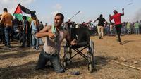 Seorang pria Palestina bernama Saber al-Ashkar menyiapkan batu saat terlibat bentrok dengan pasukan Israel di dekat perbatasan antara Israel dengan Jalur Gaza (11/5). (AFP/Mahmud Hams)