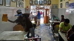 Pekerja membersihkan panel transparan yang membagi meja di restoran yang dibuka kembali usai pelonggaran lockdown di Bangalore, India, Senin (8/6/2020). Untuk keamanan pelanggan, restoran-restoran menyiapkan panel transparan sebagai bagian dari rangkaian pencegahan COVID-19. (Manjunath Kiran/AFP)