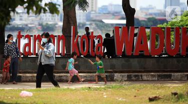 Anak-anak berlarian saat mengunjungi Taman Kota Waduk Pluit di Penjaringan, Jakarta Utara, Minggu (27/12/2020). Taman Kota Waduk Pluit dibuka kembali setelah di tutup pada libur Natal, namun banyak warga yang berwisata tidak menerapkan protokol kesehatan. (Liputan6.com/Johan Tallo)