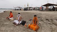 Umat Hindu menutup wajah mereka dengan kain untuk mencegah terpapar virus corona COVID-19 saat melakukan ritual selama gerhana matahari di pertemuan Sungai Gangga dan Sungai Yamuna di Sangam, Prayagraj, India, Minggu (21/6/2020). (AP Photo/Rajesh Kumar Singh)