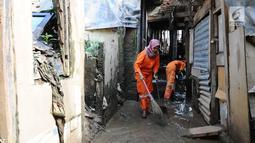 Petugas PPSU Kelurahan Kampung Melayu Siti Hajar saat membersihkan sisa lumpur akibat banjir yang melanda Kebon Pala, Jakarta, Kamis (25/4). Karena kecintaannya dengan kebersihan, Siti Hajar ingin membuat lingkungan Jakarta lebih bersih dan indah. (Liputan6.com/Herman Zakharia)