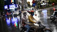 Seorang penumpang berlindung di bawah kantong plastik dengan pengemudi ojek saat hujan di Hanoi, ibu kota Vietnam pada 11 Agustus 2020. Setelah mencatat nol kasus COVID-19 selama lebih dari tiga bulan, Vietnam melaporkan sejumlah infeksi baru di dalam negeri sejak akhir Juli. (MANAN VATSYAYANA/AFP)