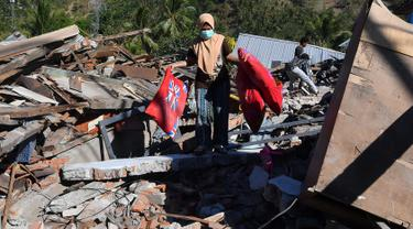 Seorang perempuan membawa bantal melalui puing-puing rumah yang rusak di Menggala, Lombok Utara, Rabu (8/8). Laporan terakhir mengatakan, gempa Lombok telah memakan 105 korban jiwa, dan lebih 70.000 orang kehilangan tempat tinggal. (AFP/ADEK BERRY)