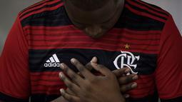 Seorang pria mengenakan jersey Flamengo berdoa saat Misa peringatan untuk para korban kebakaran di akademi sepakbola Brasil, di Rio de Janeiro, Brasil (8/2). Kebakaran tersebut menewaskan 10 pemain muda dan tiga luka-luka. (AP Photo/Leo Correa)