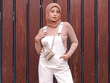Gaya OOTD berhijab Awkarin bisa jadi inspirasi dengan memadukan busana berwarna pink soft dengan jumpsuit putih ini. Hijab simpel berwarna senada menambah gaya casual (Liputan6.com/IG/@awkarin)