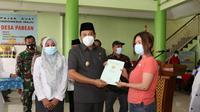 Wakil Bupati (Wabup) Sidoarjo Subandi menyerahkan sertifikat tanah kepada warga Desa Pabean Sedati. (Dian Kurniawan/Liputan6.com)