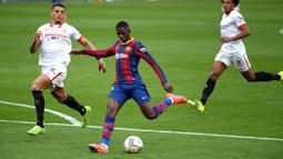 Peluang pertama Barcelona hadir pada menit ke-21. Ousmane Dembele (tengah) melepas tembakan kaki kirinya tapi bola masih bisa ditangkap oleh penjaga gawang Sevilla. (Foto: AFP/Cristina Quicler)