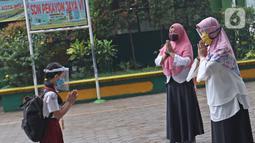 Seorang murid memberi salam kepada guru saat memasuki sekolah  SD Negeri 6, Bekasi, Jawa Barat, Selasa (4/8/2020). Pemerintah setempat memberikan izin kepada enam sekolah untuk melakukan uji coba pembelajaran tatap muka selama satu bulan. (Liputan6.com/Herman Zakharia)