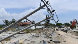 Tiang-tiang listrik roboh usai gempa dan tsunami melanda Kabupaten Sigi, Sulawesi Tengah, Kamis (4/10). Badan Nasional Penanggulangan Bencana (BNPB) mengatakan beberapa lokasi di Sigi terisolir akibat gempa dan tsunami. (ADEK BERRY/AFP)