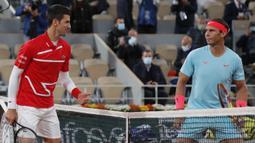 Petenis Novak Djokovic (kiri) dan Rafael Nadal saling memandang sebelum pertandingan final Prancis Terbuka 2020 di Stadion Roland Garros, Paris, Prancis, Minggu (11/10/2020). Dengan kemenangan ini, Nadal menyamai rekor Roger Federer dengan meraih 20 gelar Grand Slam. (AP Photo/Michel Euler)