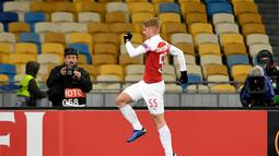 Selebrasi pemain muda Arsenal, Emile Smith Rowe usai mencetak gol pertama ke gawang Vorskla pada laga lanjutan Grup E Liga Europa yang berlangsung stadion NSK Olimpiyskiy, Kyiv, Jumat (30/11). Arsenal menang atas Vorskla 3-0. (AFP/Sergei Supinsky)