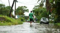 Penduduk mengarungi jalan-jalan yang banjir di ibu kota Fiji Suva pada 16 Desember 2020, menjelang topan super Yasa. (Foto: AFP / Leon Lord)