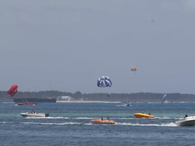 Turis menikmati permainan Parasailing di pantai Nusa Dua Bali, Rabu (10/10). Penyelenggaraan IMF - Bank Dunia Bali 2018 diharapkan dapat memberi imbas lebih baik di Indonesia khususnya sektor pariwisata. (Liputan6.com/Angga Yuniar)