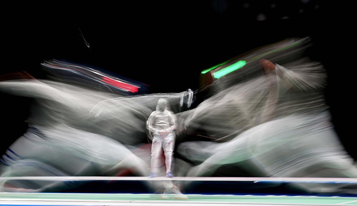 Atlet Anggar asal Italia Luca Curatoli (kiri) bertanding melawan Iulian Teodosiu dari Rumania dalam kualifikasi men's sabre individual  Olimpiade Tokyo 2020 di Makuhari Messe Hall, Prefektur Chiba, Jepang, Sabtu (24/7/2021). (Foto: AFP/Mohd Rasfan)