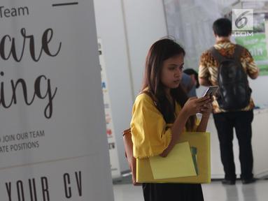 Pencari kerja melihat-lihat ponsel saat gelaran Job For Career Festival 2019 di area Stadion GBK, Jakarta, Selasa (5/3). Berdasarkan data BPS per Agustus 2018 sebanyak tujuh juta orang Indonesia menganggur. (Liputan6.com/Helmi Fithriansyah)