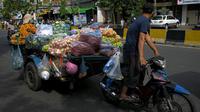 Seorang pedagang mengendarai kereta motornya yang berisi sayuran untuk dijual karena pasar tetap ditutup di tengah pembatasan lockdown yang diberlakukan untuk mencoba menghentikan lonjakan kasus virus corona COVID-19 di Phnom Penh, Kamboja, Selasa (11/5/2021). (TANG CHHIN Sothy/AFP)