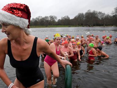 Sejumlah perenang naik meninggalkan danau usai mengikuti lomba berenang di Danau Serpentine di Hyde Park, London, Inggris, Minggu (25/12). Lomba ini digelar untuk merayakan Natal 2016. (REUTERS/Toby Melville)