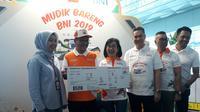 Direktur Bisnis Konsumer BNI Tambok P Setyawati (kedua kanan) menyerahkan mock-up tiket pesawat Garuda Indonesia kepada perwakilan pemudik pesawat Doddy Hertanto (kedua kiri) di Bandara Internasional Soekarno Hatta. Dok: Pramita Tristiawati