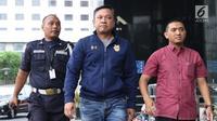 Bupati Pakpak Bharat Sumatera Utara, Remigo Yolanda Berutu (tengah) digiring petugas saat tiba di Gedung KPK, Jakarta, Minggu (18/11). Remigo terkena OTT terkait dugaan penerimaan suap proyek di Dinas PUPR. (Liputan6.com/Helmi Fithriansyah)