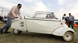 Seorang pria mendorong mobil model 'Kabinenroller' klasik Messerschmitt KR200 selama Pertemuan Klasik Kairo ke-7 di Kairo, Mesir (23/3). (Reuters/Mohamed Abd El Ghany)