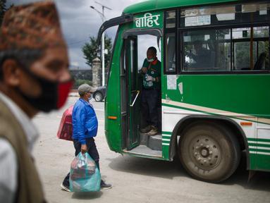 Calon penumpang bersiap naik bus di Kathmandu, Nepal (16/7/2020). Beberapa perusahaan angkutan umum di Lembah Kathmandu sudah mulai mengoperasikan kembali rute mereka untuk pertama kalinya dalam hampir empat bulan setelah menerima persyaratan operasional dari pemerintah. (Xinhua/Sulav Shrestha)