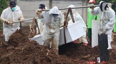 Petugas membawa peti berisi jenazah dengan protokol COVID-19 di TPU Srengseng Sawah, Jakarta, Kamis (21/1/2021). Sebagian lahan TPU Srengseng Sawah yang dijadikan lokasi pemakaman jenazah Covid-19 sejak Selasa (12/1) lalu, kini hanya tersisa 79 petak makam. (Liputan6.com/Helmi Fithriansyah)