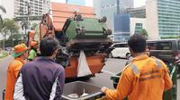 Petugas kebersihan tengah membersihkan sisa CFD di Bundaran HI yang sudah bersih dari PKL, Minggu (3/11/2019). (Liputan6.com/Yopi Makdori)