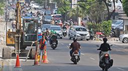Kondisi lalu lintas saat pekerja menyelesaikan proyek revitalisasi trotoar di kawasan Kemang, Jakarta, Jumat (29/6/2019). Kepala Dinas Binamarga DKI Jakarta mengatakan anggaran pembenahan trotoar Kemang dan Jalan Prof Doktor Satrio Jakarta Selatan capai Rp 100 miliar. (Liputan6.com/Herman Zakharia)