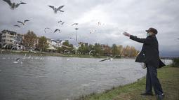 Seorang pria memberi makan kawanan burung yang bermigrasi di tepi sebuah sungai di Tonekabon, Iran utara, pada 30 November 2020. (Xinhua/Ahmad Halabisaz)