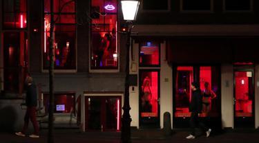 Orang-orang berjalan melewati rumah bordil di Red Light District Amsterdam, Belanda, Rabu (3/4). Red Light District merupakan kawasan prostitusi yang tersohor dan menjadi salah satu destinasi wisata di Belanda. (REUTERS/Yves Herman)