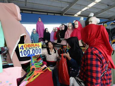 Pengunjung memilih busana muslim di skybridge Tanah Abang, Jakarta, Rabu (8/5/2019). Hari ketiga puasa bulan Ramadan, Warga Jakarta dan penyangga sekitarnya sudah mulai berbelanja pakaian muslim dengan harga yang murah untuk kebutuhan sendiri atau untuk dijual kembali. (Liputan6.com/Herman Zakharia)
