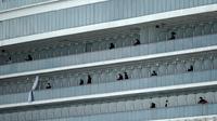 Aktivitas penumpang kapal pesiar Diamond Princess yang dikarantina di sebuah pelabuhan di Yokohama, Jepang, Rabu (19/2/2020). Satu WNI di kapal pesiar Diamond Princess kembali dinyatakan positif terinfeksi virus corona (COVID-19). (AP Photo/Eugene Hoshiko)