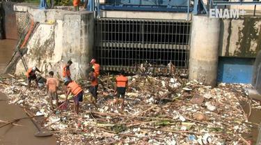 Banjir yang melanda Jakarta menyisakan sampah, pasukan oranye berjibaku membersihkan sampah meskipun kondisi aliran sungai masih deras