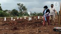 Pihak keluarga usai melakukan ziarah di area khusus pemakaman jenazah dengan protokol COVID-19 di TPU Srengseng Sawah Dua, Jakarta, Selasa, (2/2/2021). TPU Srengseng Sawah 2, saat ini mulai menerima pemakaman jenazah protokol COVID-19 dengan kapasitas 1.020 petak. (Liputan6.com/Helmi Fithriansyah)