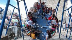 Anak-Anak Suriah Rayakan Idul Fitri di Taman Bermain: Anak-anak Suriah bermain di taman hiburan sementara ketika merayakan Idul Fitri di kota Idlib, Senin (24/5/2020). Anak-anak itu menikmati permainan yang mungkin jarang mereka rasakan di tengah peperangan yang masih berkecamuk. (OMAR HAJ KADOUR/A