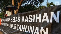 Aktivis JSKK membentangkan spanduk saat menggelar aksi Kamisan ke-589 di depan Istana Merdeka, Jakarta, Kamis (20/6/2019). Dalam aksinya, JSKK meminta Presiden Joko Widodo memegang teguh komitmen untuk menyelesaikan pelanggaran HAM berat masa lalu. (Liputan6.com/Johan Tallo)