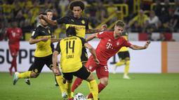 Bek Dortmund, Nico Schulz, berusaha merebut bola dari bek Bayern Munchen, Joshua Kimmich, pada laga Piala Super DFL di Stadion Signal Iduna, Dortmund, Sabtu (3/8). Dortmund menang 2-0 atas Munchen. (AFP/Ina Fassbender)