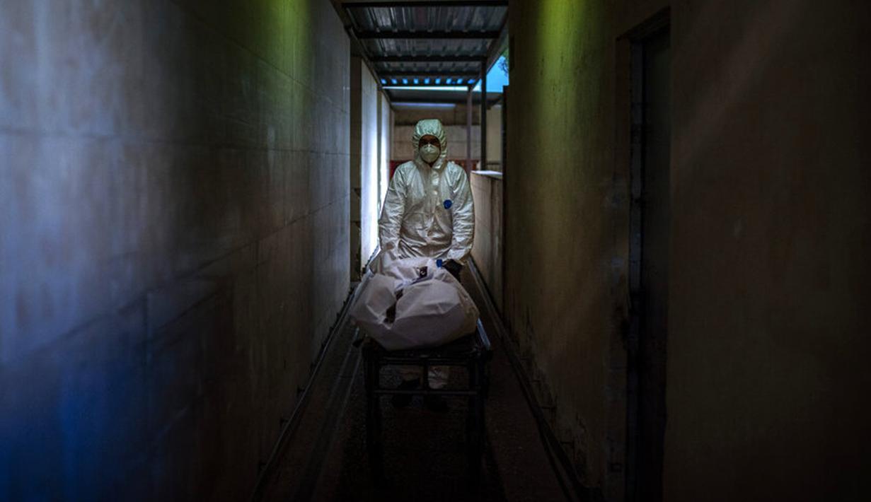 Petugas kamar jenazah membawa jenazah korban COVID-19 di kamar jenazah sebuah rumah sakit di Barcelona, Spanyol, 5 November 2020. Seperti dokter dan perawat, petugas kamar jenazah adalah bagian dari sekelompok pekerja penting di tengah pandemi. (AP Photo/Emilio Morenatti)