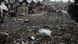 Sejumlah warga membersihkan jalan yang tertutup sampah usai Badai Matthew menghantam Port-au-Prince di Haiti (4/10). Keganasan Badai Matthew ini telah meluluhlantakkan wilayah Haiti. (REUTERS/Carlos Garcia Rawlins)