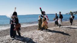 Orang-orang yang mengenakan kostum era Napoleon Bonaparte berjalan di pantai dalam rangka peringatan 200 tahun kematian Napoleon Bonaparte di Saint-Helene, Golfe-Juan, Prancis, 16 Maret 2021. Sebagai Napoleon I, ia adalah Kaisar Prancis dari tahun 1804-1814, dan kembali pada 1815. (Valery HACHE/AFP)