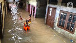 Anak-anak bermain di tengah banjir yang merendam kawasan Kebon Pala, Jakarta Timur, Selasa (25/2/2020). Akibat banjir yang tak kunjung surut, aktivitas warga di kawasan tersebut menjadi terganggu, terlebih dengan adanya pemadaman listrik. (Liputan6.com/Immanuel Antonius)