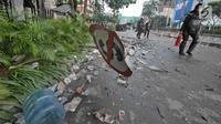Aparat keamanan melintas di antara sisa kerusuhan di kawasan Wahid Hasyim, Jakarta, Kamis (23/5/2019). Massa yang ricuh di depan Kantor Bawaslu dipukul mundur oleh polisi hingga berhamburan ke sejumlah titik dekat lokasi. (Liputan6.com/Herman Zakharia)